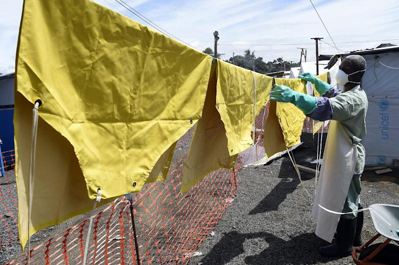 A health worker in protective gear hangs aprons to dry on October 1, 2014 at a treatment centre in Liberia's capital Monrovia (AFP Photo/Pascal Guyot)