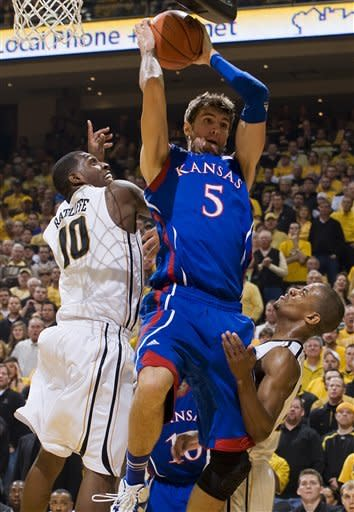 Kansas' Jeff Withey, center, pulls down a rebound as he is squeezed between Missouri's Kim English, right, and Ricardo Ratliffe, left, during the second half of an NCAA college basketball game on Saturday, Feb. 4, 2012, in Columbia, Mo. Missouri won the game 74-71. (AP Photo/L.G. Patterson)