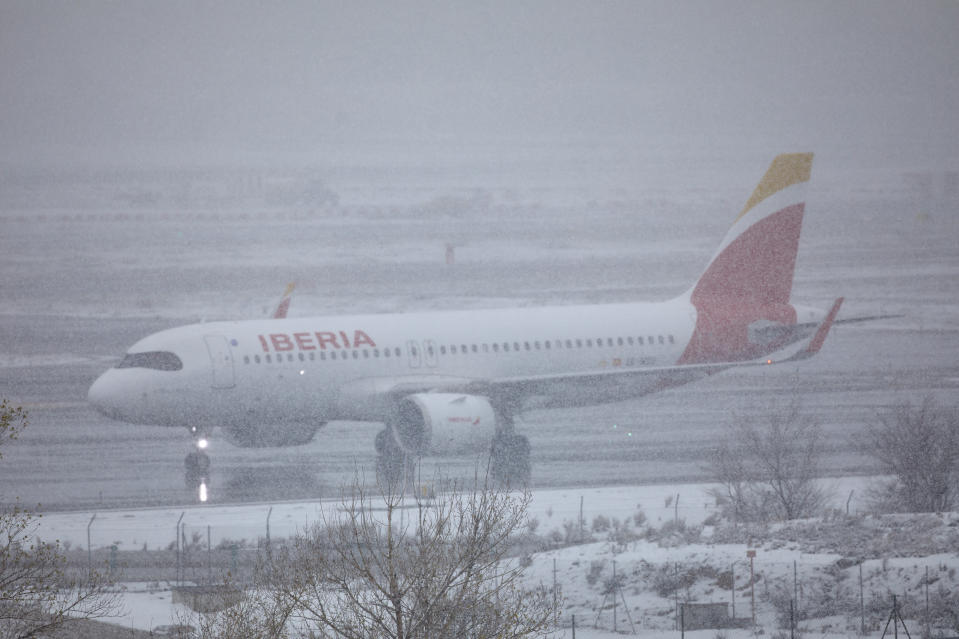 A passenger plane is seen on the ground of the Madrid airport during a heavy snowfall in downtown, Spain, Saturday, Jan. 9, 2021. A persistent blizzard has blanketed large parts of Spain with 50-year record levels of snow, halting traffic and leaving thousands trapped in cars or in train stations and airports that suspended all services as the snow kept falling on Saturday. (Jesus Hellin/Europa Press via AP)