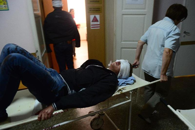 An injured man arrives on a stretcher at hospital after a shelling in Donetsk, eastern Ukraine on October 1, 2014 (AFP Photo/John MacDougall)