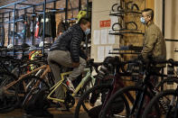 Customers wearing face masks to help curb the spread of the coronavirus chat each other as they try out the American bicycle brand at a retail shop in Beijing Tuesday, March 2, 2021. Chinese leaders are shifting focus from the coronavirus back to long-term goals of making China a technology leader at this year's highest-profile political event, the meeting of its ceremonial legislature, amid tension with Washington and Europe over trade, Hong Kong and human rights. (AP Photo/Andy Wong)