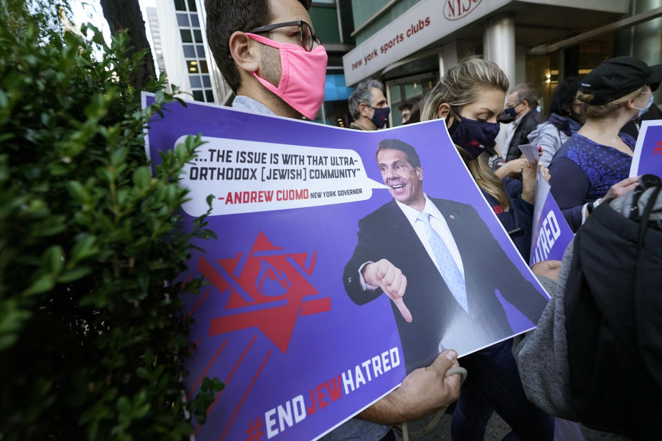 """A manholds a sign as he joins protesters outside the offices of New York Gov. Andrew Cuomo, Thursday, Oct. 15, 2020, in New York. Three Rockland County Jewish congregations are suing New York state and Gov. Andrew Cuomo, saying Cuomo engaged in a """"streak of anti-Semitic discrimination"""" with a recent crackdown on religious gatherings to reduce the state's coronavirus infection rate. (AP Photo/Kathy Willens)"""