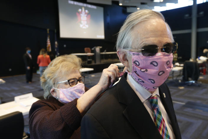 Virginia Senate Clerk Susan Schaar, ties a mask on Virginia State Senator Thomas Norment, R-James City County, as they prepare for the reconvene session at the Science Museum of Virginia Wednesday April 22, 2020, in Richmond, Va. The Senate is meeting in a remote location due to COVID-19 social distancing restrictions. (AP Photo/Steve Helber, Pool)