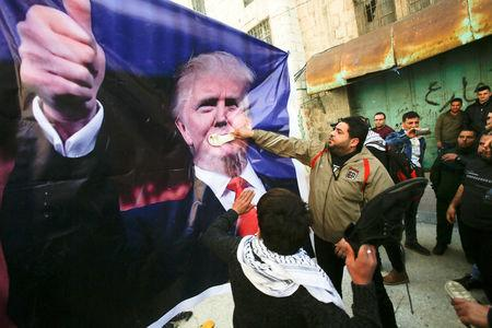 FILE PHOTO: Palestinian demonstrators throw shoes on a poster depicting U.S. President Donald Trump during a protest in the West Bank city of Hebron February 24, 2017. REUTERS/Mussa Qawasma/File Photo
