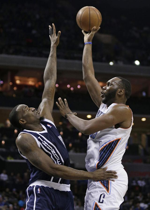 Charlotte Bobcats' Al Jefferson, right, shoots over Oklahoma City Thunder's Kendrick Perkins during the first half of an NBA basketball game in Charlotte, N.C., Friday, Dec. 27, 2013. (AP Photo/Chuck Burton)