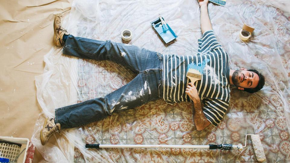 One young man is lying down on the floor after a hard days work painting his new apartment.