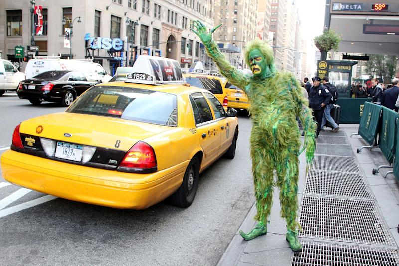 """In this Oct. 17, 2012 publicity image released by Madison Square Garden, Jeff McCarthy hails a cab dressed as The Grinch outside Madison Square Garden, where """"Dr. Seuss' How The Grinch Stole Christmas! The Musical"""" is playing this Christmas season. (AP Photo/Madison Square Garden, Amanda Schwab/Starpix)"""