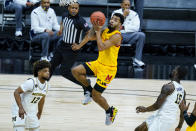 Maryland guard Eric Ayala (5) shoots over Michigan guards Mike Smith (12) and Chaundee Brown (15) in the first half of an NCAA college basketball game at the Big Ten Conference tournament in Indianapolis, Friday, March 12, 2021. (AP Photo/Michael Conroy)