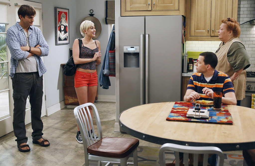 "Hey, Alan and Berta want to meet Miley Cyrus, too! Missi and her very tiny shorts step into the iconic ""Two and a Half Men"" kitchen to meet Alan (Jon Cryer) and Berta (Conchata Ferrell), with Walden looking sheepish in the background. (Is this post-bed scene, we wonder?)"