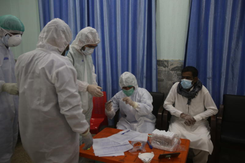 Health officials in protective gear take a sample from a man at a screening and testing facility for COVID-19 in Peshawar, Pakistan, Wednesday, June 3, 2020. (AP Photo/Muhammad Sajjad)