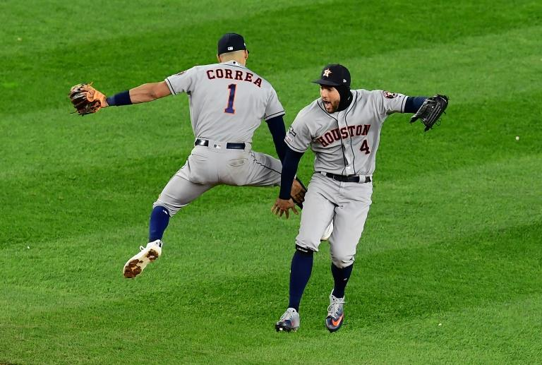 Houston's Carlos Correa and George Springer celebrate the Astros' 8-3 victory over the New York Yankees which moved the Texas team within one win of a Major League Baseball World Series berth (AFP Photo/Emilee Chinn)