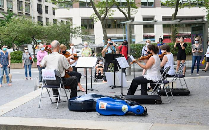 People gather to watch a surprise outdoor performance by the New York Philharmonic - Noam Galai