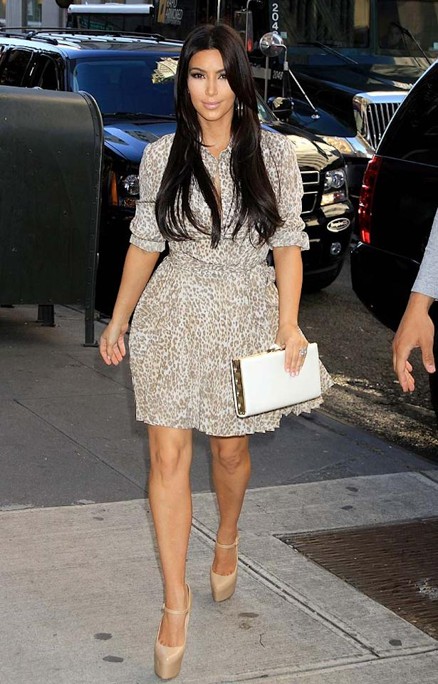 Khloe's sister Kim was snapped in NYC wearing rather demure leopard-print dress in NYC. Nude platform heels and sleek tresses completed her cute look. (10/05/2011)