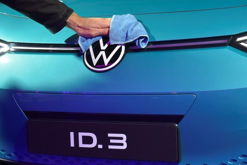 An employee cleans a logo of a new car after a ceremony marking start of the production of a new electric Volkswagen model ID.3 in Zwickau