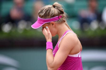 Eugenie Bouchard wipes her face dejected during her 1st round women's singles match against Kristina Mladenovic on day three of the French Open at Roland Garros on May 26, 2015 in Paris, France