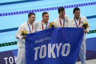 """Members of the U.S. men's 4x100-meter medley relay team, Caeleb Dressel, Zach Apple, Ryan Murphy and Michael Andrew, carry a sign that reads, """"Thank you, Tokyo,"""" after winning the gold medal at the 2020 Summer Olympics, Sunday, Aug. 1, 2021, in Tokyo, Japan. (AP Photo/Jae C. Hong)"""