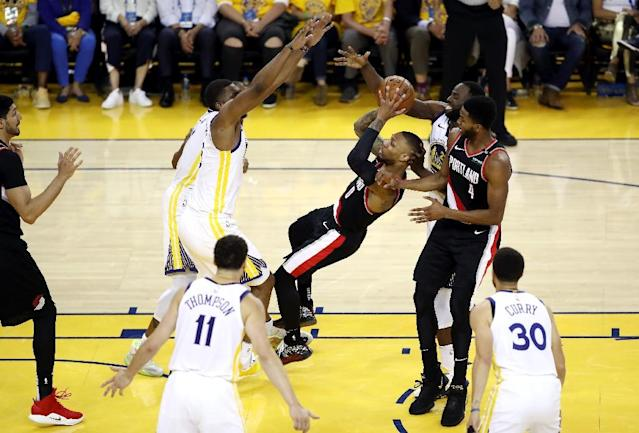 Defense: Portland's Damian Lillard tries to get a shot off in the Trail Blazers' 116-94 loss to the Golden State Warriors in game one of the NBA Western Conference Finals (AFP Photo/EZRA SHAW)