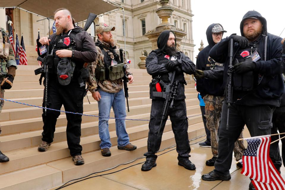 "Michael Null (R) and William Null (L) arrive at the American Patriot Rally, organized by Michigan United for Liberty, to demand the reopening of businesses on the steps of the Michigan State Capitol in Lansing, Michigan, on April 30, 2020. Other men are unidentified. - Thirteen men, including members of two right-wing militias, have been arrested for plotting to kidnap Michigan Governor Gretchen Whitmer and ""instigate a civil war"", Michigan Attorney General Dana Nessel announced on October 8, 2020. The Nulls were charged for their alleged roles in the plot to kidnap Whitmer, according to the FBI. The brothers are charged with providing support for terroristic acts and felony weapons charges. (Photo by JEFF KOWALSKY / AFP) (Photo by JEFF KOWALSKY/AFP via Getty Images)"