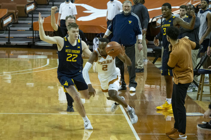 Texas guard Matt Coleman, III (2) is fouled by West Virginia guard Sean McNeil (22) at the end of the second half of an NCAA college basketball game, Saturday, Feb. 20, 2021, in Austin, Texas. (AP Photo/Michael Thomas)