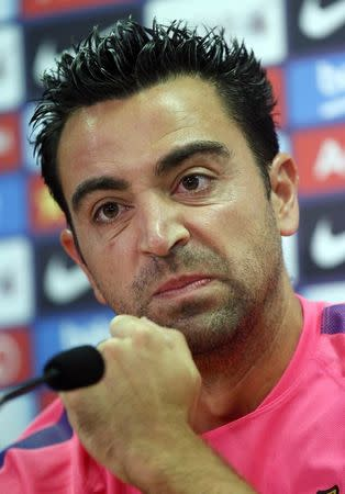 FC Barcelona's player Xavi Hernandez gestures during a news conference at Joan Gamper training camp, near Barcelona August 5, 2014. Spain midfielder Xavi has retired from internationals at the age of 34, he said on Tuesday. The Barcelona player represented his country a record 133 times and helped Spain win the 2010 World Cup and the 2008 and 2012 European Championships. REUTERS/Albert Gea
