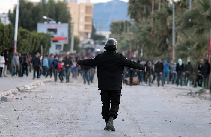 FILE - This Saturday, Dec. 1, 2012 file photo shows Tunisian protesters clashing with riot police, in Siliana, Tunisia. Two years after the revolution that overthrew a dictator and started the Arab Spring, Tunisia is struggling with high unemployment and rising violence in its politics. After sounding the alarm for months over the rise of religious extremists, the opposition now warns that the new threat to this North African country's democratic transition are vigilante bands allied to the elected government. (AP Photo/Amine Landoulsi, File)