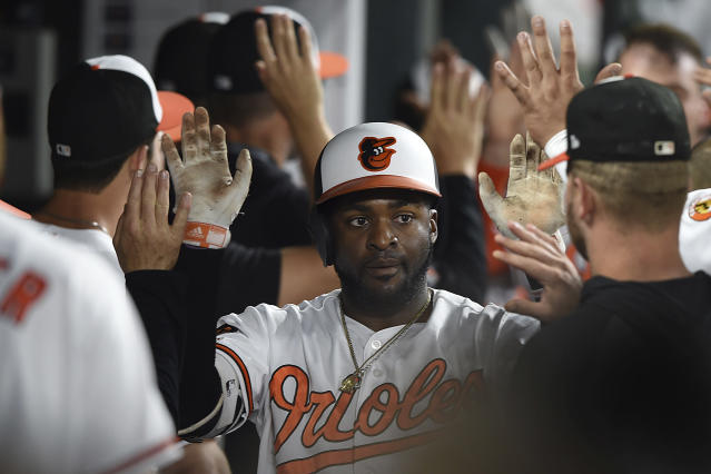 Baltimore Orioles' Dwight Smith Jr. is congratulated in the dugout after hitting a three run home run against the Chicago White Sox in the fourth inning of a baseball game, Tuesday, April 23, 2019, in Baltimore. (AP Photo/Gail Burton)