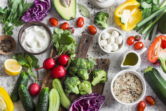 Balanced healthy diet food background in a Mediterranean style. Fresh vegetables, wild rice, fresh yogurt and goat cheese on a light background, top view. Flat lay