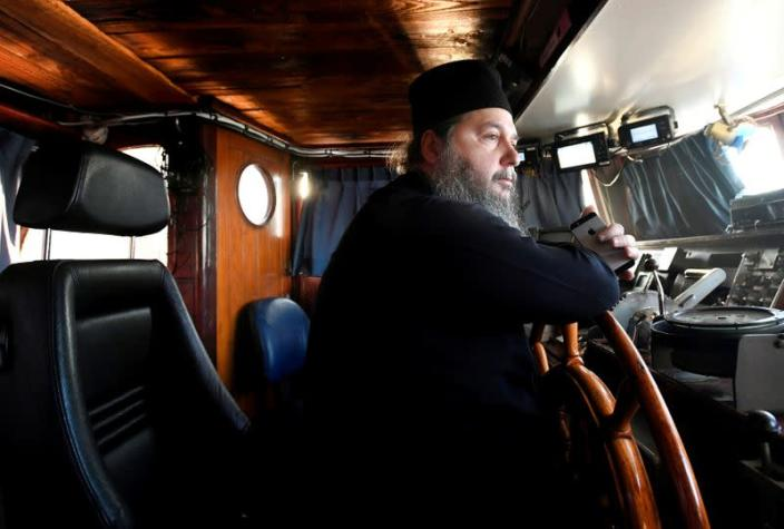 Father Abbot Abibos looks out the window from the wheelhouse of a mobile Georgian Orthodox monastery in Vlissingen