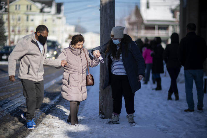 Maria Manazaz, center, is helped by Manny Riposa, left, and a fellow resident to get in line for her vaccine at a clinic in Central Falls, R.I., Saturday Feb. 20, 2021. Nearly a third of adults in the city have received at least one dose of vaccine, according to state data. Health officials say the city of about 20,000 has seen a marked drop in COVID-19 cases as a result. (AP Photo/David Goldman)