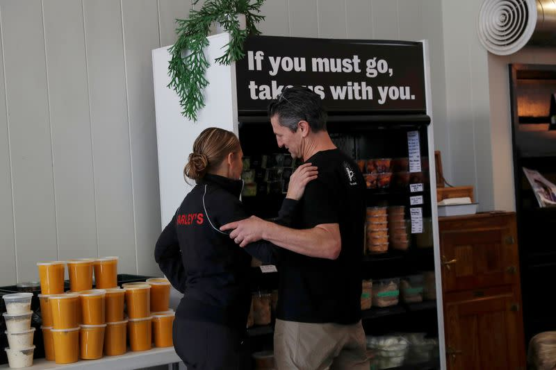 FILE PHOTO: Amy and Chris Hillyard, owners of Farley's East cafe that closed due to the financial crisis caused by the coronavirus disease (COVID-19), embrace at the cafe in Oakland, California