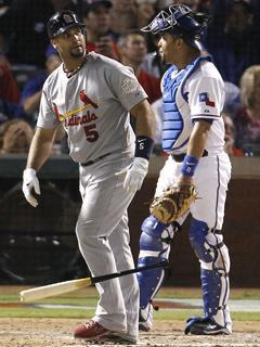 Rangers catcher Yorvit Torrealba looks away in dismay as Albert Pujols watches his sixth-inning homer in Game 3 of the World Series