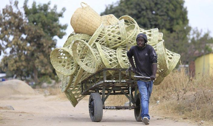 A man pulls a cart laden with reed chairs in an impoverished settlement of Hopley, Harare, Zimbabwe - Wednesday 23 June 2021