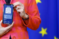 FILE - In this June 16, 2021, file photo, European Commission President Ursula von der Leyen shows a phone, as she gives a press statement on the new COVID-19 digital travel certificate at the European Commission headquarters in Brussels. In both the U.S. and the EU, officials are struggling with the same question: how to boost vaccination rates to the max and end a pandemic that has repeatedly thwarted efforts to control it. In the European Union, officials in many places are requiring people to show proof of vaccination, a negative test or recent recovery from COVID-19 to participate in everyday activities — even sometimes to go to work. (Johanna Geron/Pool Photo via AP, File)