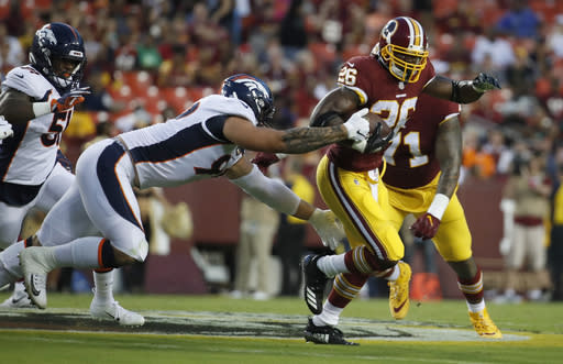 Washington Redskins running back Adrian Peterson (26) gets away from Denver Broncos defensive end Adam Gotsis (99) during the first half of a preseason NFL football game Friday, Aug. 24, 2018, in Landover, Md. (AP Photo/Alex Brandon)