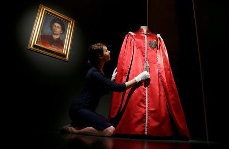 A member of the Royal Collection Trust, poses for photographers next to Britain's Queen Elizabeth's 'Mantle of The Order of The British Empire' robe, ahead of the opening of an exhibition entitled 'Fashioning a Reign: 90 Years of Style from the Queen's Wardrobe', at Buckingham Palace, in London, Britain July 21, 2016. REUTERS/Peter Nicholls