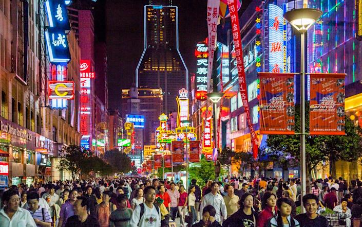 China, Shanghai, nightview of Nanjing Road pedestrian zone, one of the world's busiest shopping streets - Manfred Gottschalk/Getty Images Contributor