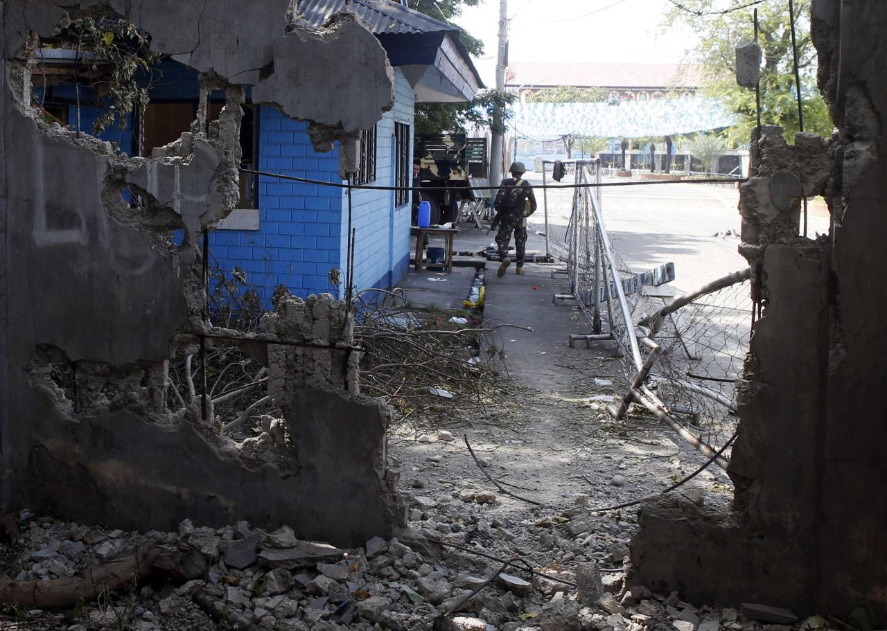 A government soldier stands guard outside a tourist police station in Fort Pilar near a wall destroyed by fighting with Muslim rebels from the Moro National Liberation Front (MNLF) in Zamboanga city in southern Philippines September 15, 2013. REUTERS/Erik De Castro (PHILIPPINES - Tags: CIVIL UNREST CONFLICT POLITICS MILITARY CRIME LAW TRAVEL)