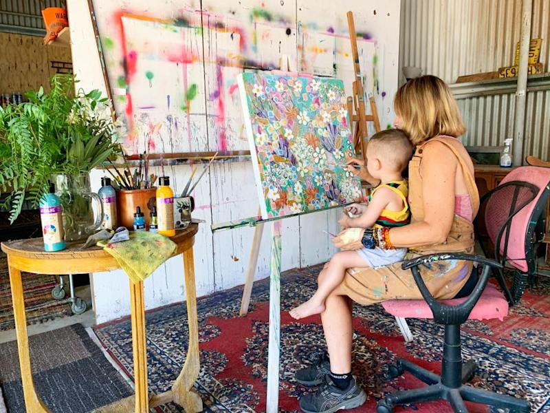 Jacinta Haycock paints with a child on her knee in a studio, a bright flower landscape