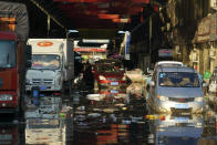 Vehicles sit in floodwaters at the Yubei Agricultural and Aquatic Products World in Xinxiang in central China's Henan Province, Monday, July 26, 2021. Record rain in Xinxiang last week left the produce and seafood market soaked in water. Dozens of people died in the floods that immersed large swaths of central China's Henan province in water. (AP Photo/Dake Kang)