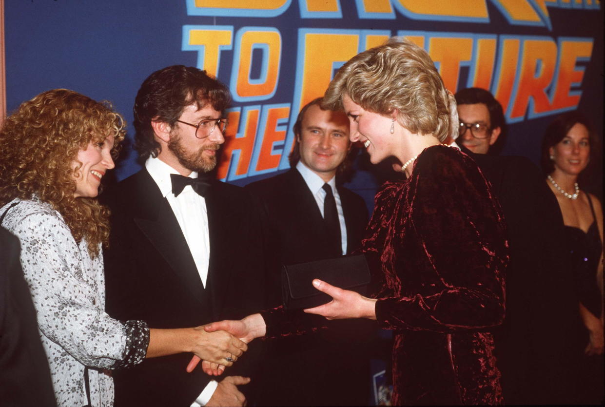 LONDON, UNITED KINGDOM - DECEMBER 03:  The Princess Of Wales Attends The Premiere Of 'back To The Future' At The Empire Cinema, Leicester Square, London Wearing A Burgundy Velvet Evening Dress Designed By Fashion Designer Catherine Walker.  She Met Steven Spielberg And His Wife Amy Irving Next To Spielberg Is Phil Collins  (Photo by Tim Graham Photo Library via Getty Images)