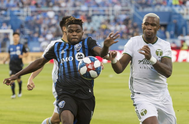 Montreal Impact's Orji Okwonkwo, left, challenges Portland Timbers' Claude Dielna during the first half of an MLS soccer game in Montreal, Wednesday, June 26, 2019. (Graham Hughes/The Canadian Press via AP)