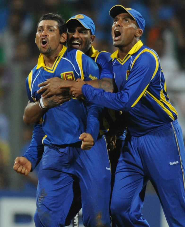 Sri Lankan cricketers Chamara Kapugedara (C) and Thisara Perera (R) greet teammate Tillakaratne Dilshan after he took a catch to dismiss unseen Indian batsman Virat Kohli during the ICC Cricket World Cup final between India and Sri Lanka at Wankhede Stadium in Mumbai on April 2, 2011. AFP PHOTO/Indranil MUKHERJEE (Photo credit should read INDRANIL MUKHERJEE/AFP/Getty Images)