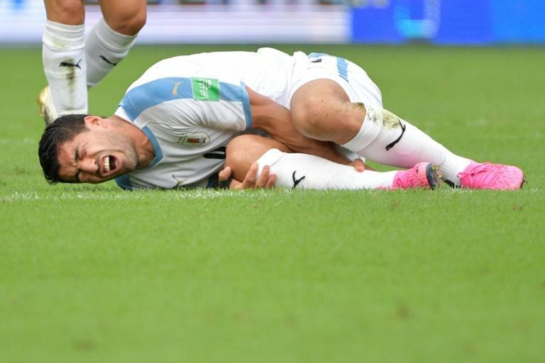 Luis Suarez nurses his ankle in the World Cup qualifying match against Colombia