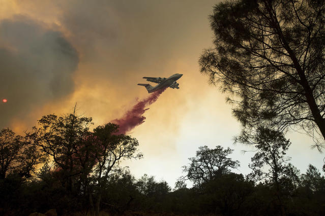 <p>A plane drops retardant while battling a wildfire near Oroville, Calif., on Saturday, July 8, 2017. The fast-moving wildfire in the Sierra Nevada foothills destroyed structures, including homes, and led to several minor injuries, fire officials said Saturday as blazes threatened homes around California during a heat wave. (AP Photo/Noah Berger) </p>
