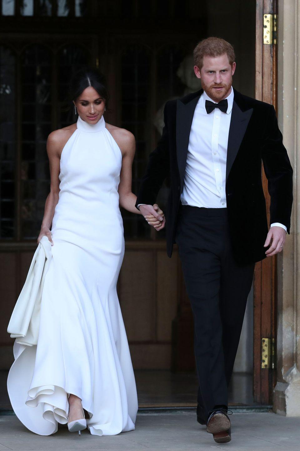 """<p>For the evening's wedding reception, Markle changed into a high-neck fishtail gown by Brit designer Stella McCartney.</p><p>The bride teamed her silk-crepe halterneck dress with <a href=""""http://www.cartier.co.uk/en-gb/collections/jewelry/collections/reflection-de-cartier/earrings/h8000215-age-d_or-de-cartier-earrings.html"""" rel=""""nofollow noopener"""" target=""""_blank"""" data-ylk=""""slk:Reflection De Cartier"""" class=""""link rapid-noclick-resp"""">Reflection De Cartier</a> diamond and white gold earrings, white court shoes and a chic chignon. </p>"""