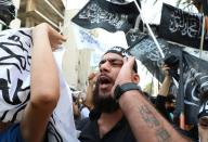 A demonstrator gestures during a protest against the cartoon publications of Prophet Mohammad in France and comments by the French President Emmanuel Macron, in Beirut