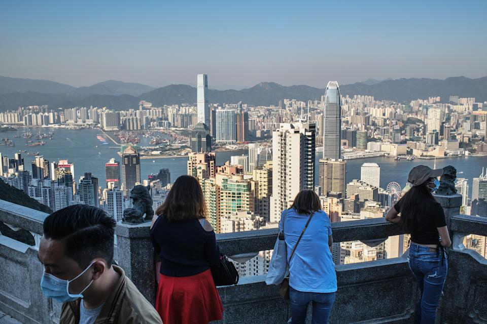 HONG KONG, CHINA - 2020/11/12: Visitors look at the skyline of Hong Kong from Victoria peak, a typically busy tourist attraction. (Photo by Isaac Wong/SOPA Images/LightRocket via Getty Images)