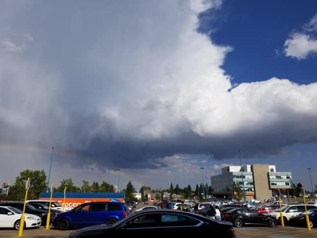 A rainbow is seen arcing below storm clouds in southwest Calgary on Sunday evening.  (Submitted to CBC - image credit)