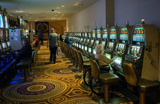 A woman plays the slot machine in a near empty casino in Atlantic City, where the closure of some casinos in recent years contributed to a sharp fall in tax revenue