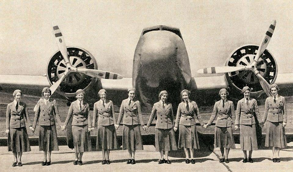 <p>An early fleet of flight attendants holds hands in front of a large twin propeller commercial airplane.</p>